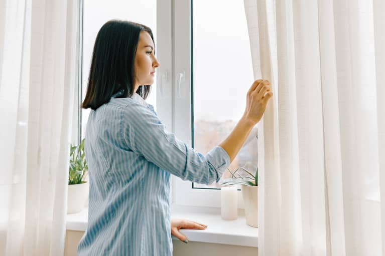 person opening curtains or lighting